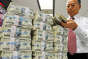 ကိုရီးယား ေငြလဲလွယ္ေရးဘဏ္တြင္ အေမရိကန္ ေဒၚလာ ရာတန္အုပ္မ်ားကို ဘဏ္အမႈထမ္းတဦး ေရတြက္ေနပံု ျဖစ္ပါသည္။ (Photo: AFP)