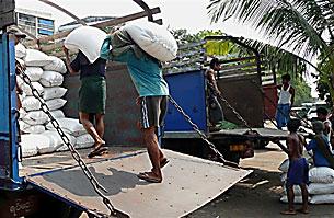ကုန်ကားပေါ်သို့ ဆန်အိတ်များ တင်နေသော ပခုံးထမ်း အလုပ်သမားများ ဖြစ်ပါသည်။