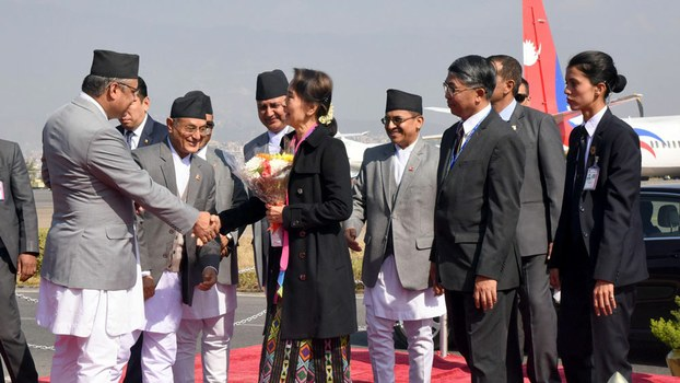 ၂ဝ၁၈ နိုဝင်ဘာလ ၂၉ ရက်နေ့က နီပေါနိုင်ငံသို့ရောက်ရှိလာသည့် မြန်မာ နိုင်ငံတော်အတိုင်ပင်ခံပုဂ္ဂိုလ် ဒေါ်အောင်ဆန်းစုကြည်ကို နီပေါဒုတိယဝန်ကြီးချုပ်နှင့် တာဝန်ရှိသူများက လေဆိပ်တွင်ကြိုဆိုနှုတ်ဆက်စဉ်။